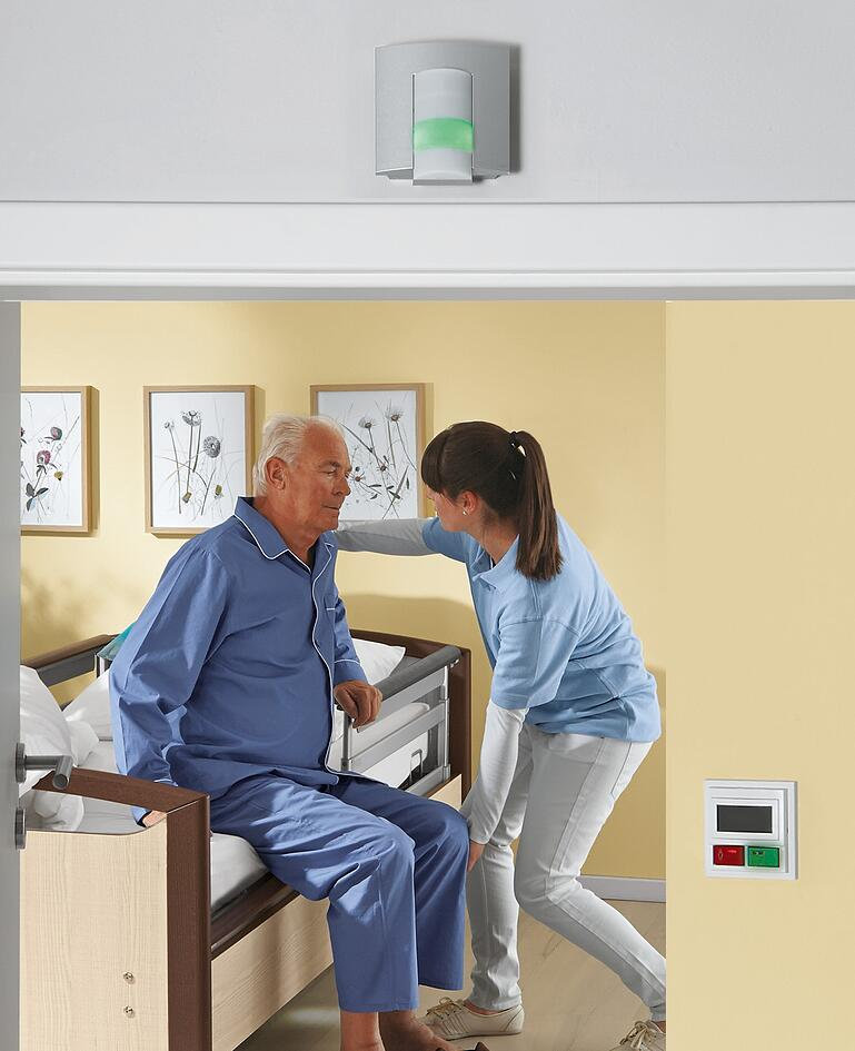 Betreuerin richtet den Mann im Niedrigpflegebett auf. Alarmsystem leuchtet grün