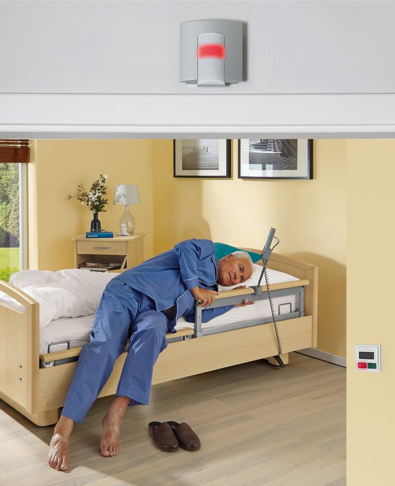 Mann liegt mit Oberkörper seitlich auf dem Niedrigpflegebett und klammert sich an die Seitensicherung. Mann hat Alarmsystem ausgelöst, das rot leuchtet