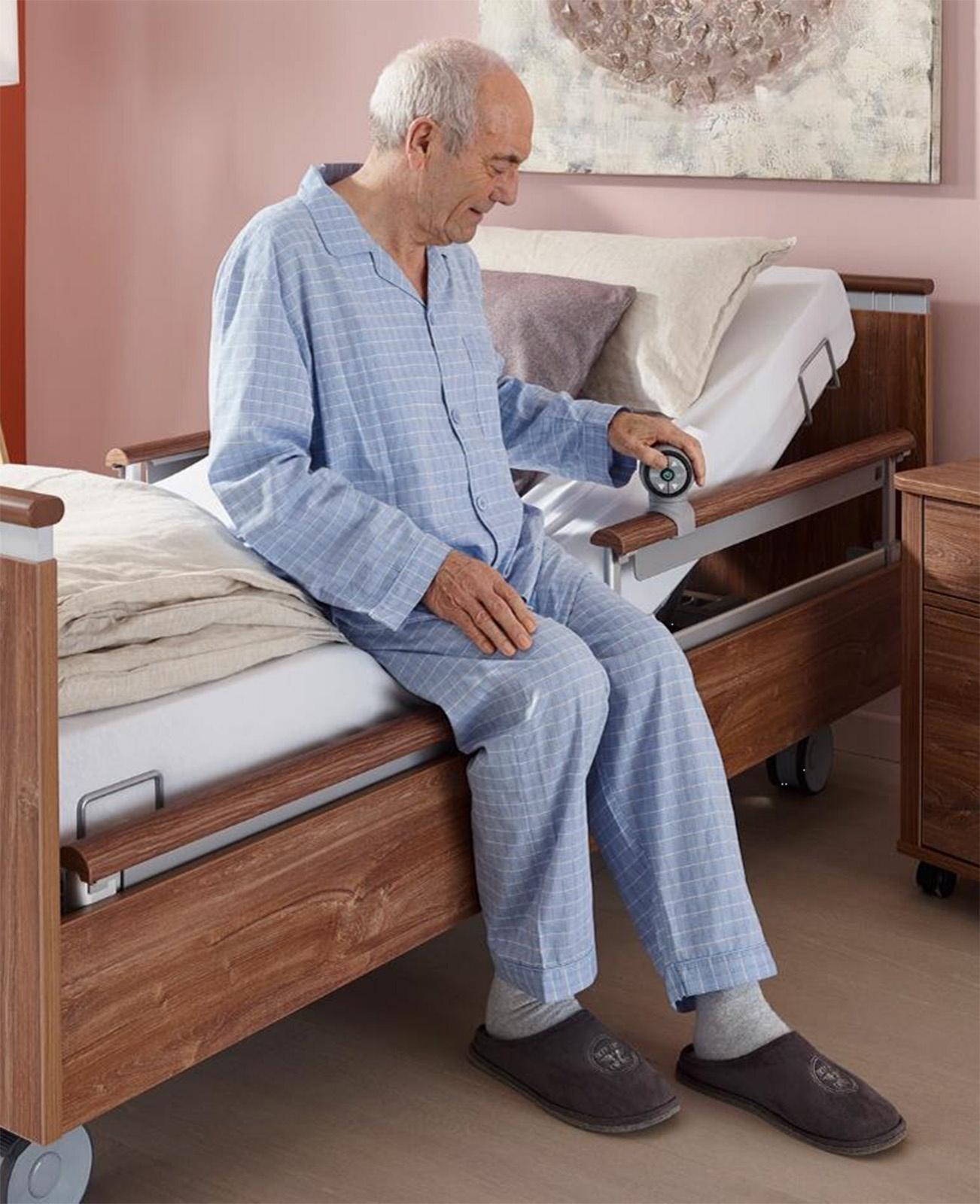 Mann hockt auf der Bettkante des Niedrigpflegebetts und bedient den SafeLift-Controller