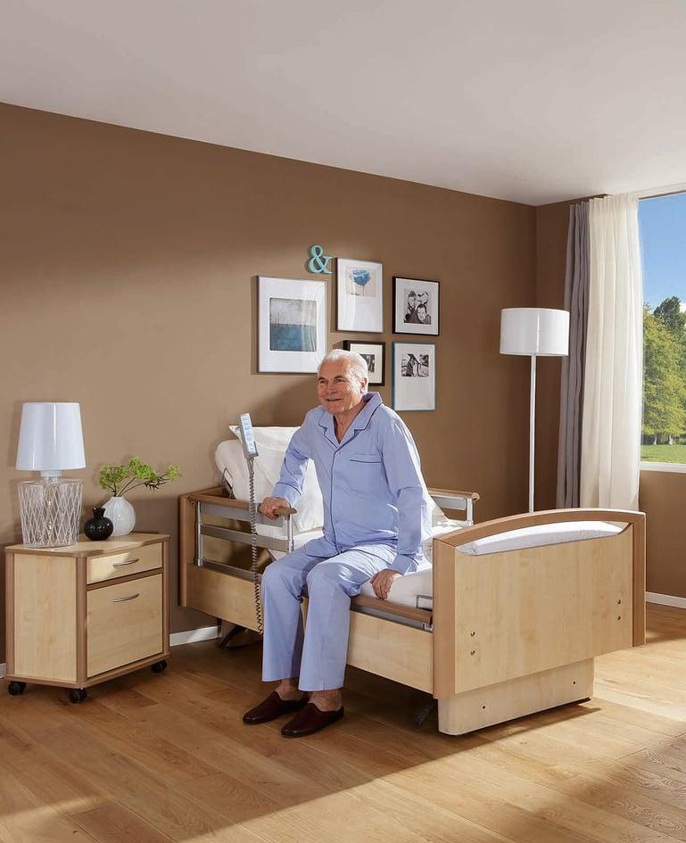 Mann im Schlafanzug sitzt auf einem demontierbaren Niedrigpflegebett und stützt sich an der Seitensicherung ab