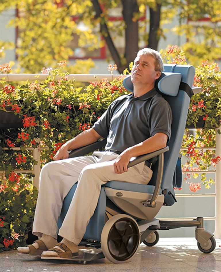 Mann ruht sich im Multifunktionsstuhl sitzend im Garten aus. Kopf lehnt an abnehmbarer Kopfstütze