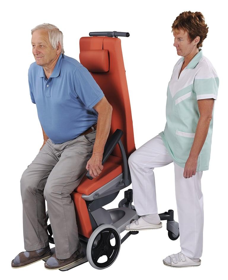 Mann steigt aus Multifunktionsstuhl auf. Betreuerin drückt Hebel zur Sitzflächenneigung, was dem Mann beim Ausstieg hilft