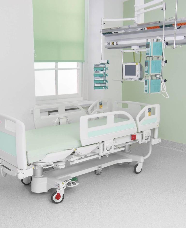 Hochfunktionales Intensivbett mit Bedienelementen in Seitensicherung. Pflegegeräte darüber an Decke befestigt