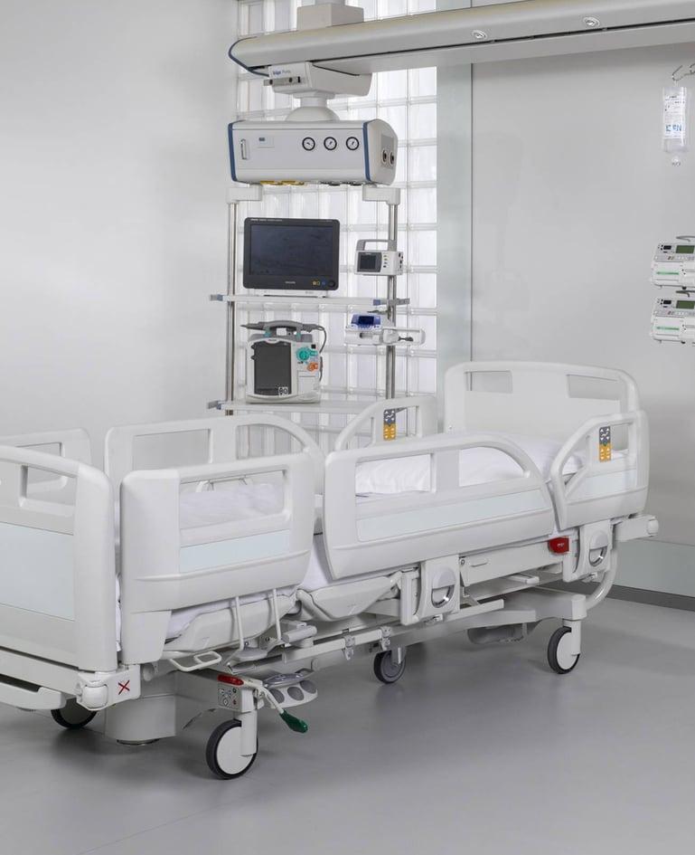 Hochfunktionales Intensivbett mit Bedienelementen in Seitensicherung. Pflegegeräte daneben auf Rollgestell.
