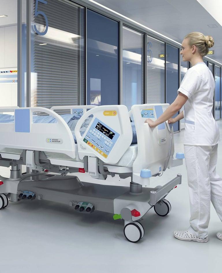 Betreuerin schiebt Person in hochfunktionalem Intensivbett mit Bedienelementen in Seitensicherung