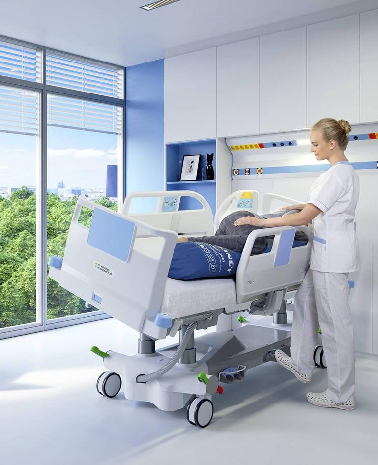 Person in lateral geschwenktem Bett. Betreuerin betreut Person, bedient Schwenkfunktion mit Fussschalter