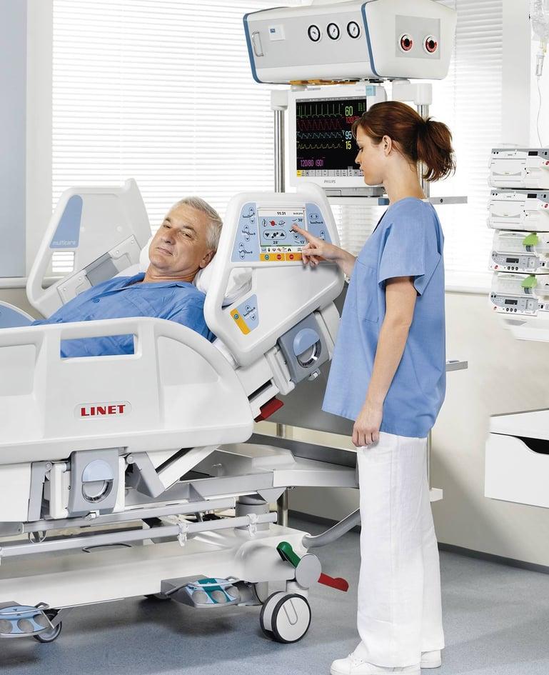 Mann liegt in Intensivbett. Krankenschwester bedient Bedienelemente in Seitensicherung