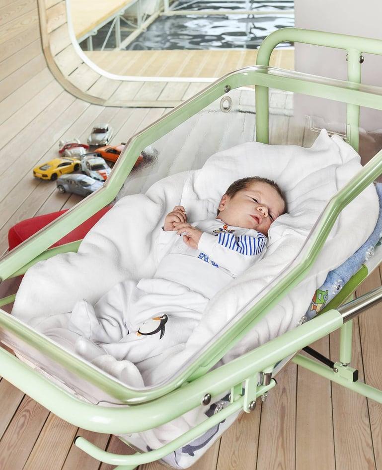 "Säugling liegt in Säuglingsschale ""mimi"" in der Farbe Grün"