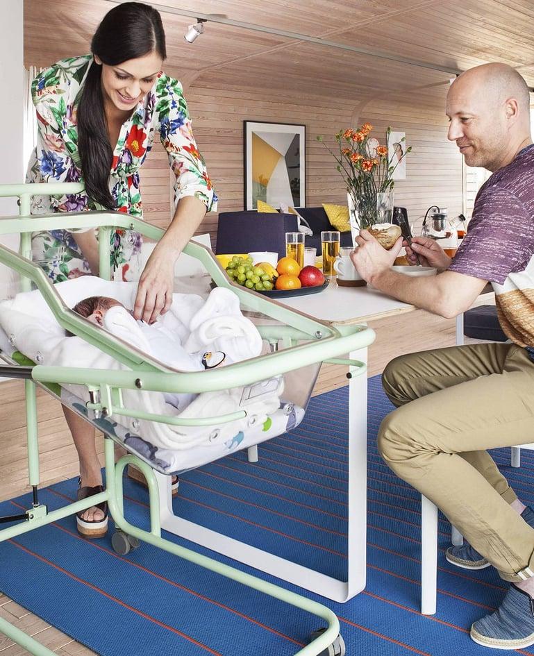 """Säugling liegt in Säuglingsschale """"mimi"""" in der Farbe Grün. Frau beugt sich über das Kind, Mann sitzt daneben"""
