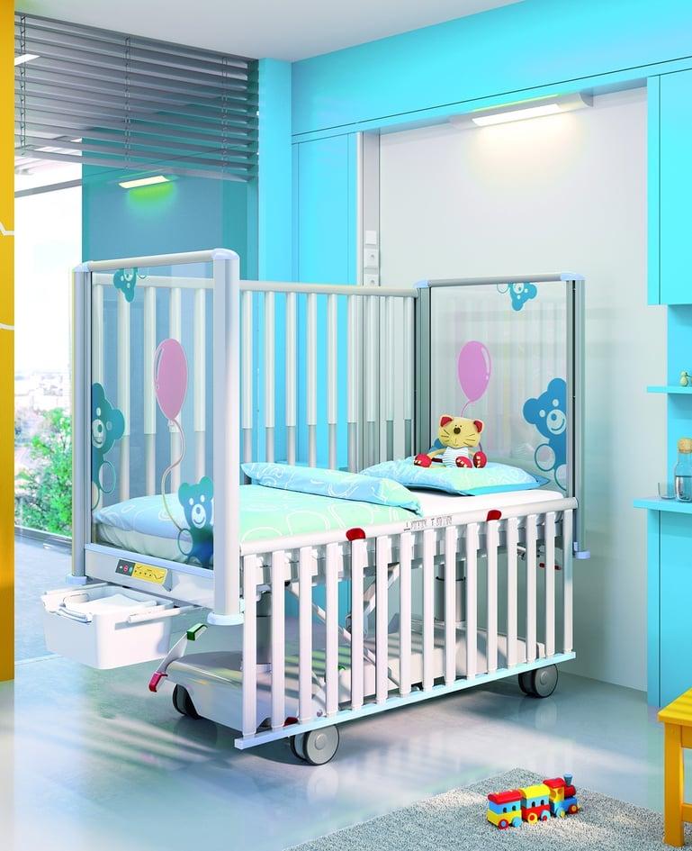 Voll elektrisch verstellbares modernes Kleinkinderbett in Blau mit Rundumsicherung. Bedienelement und ausgefahrene Bettzeugablage am Fussende