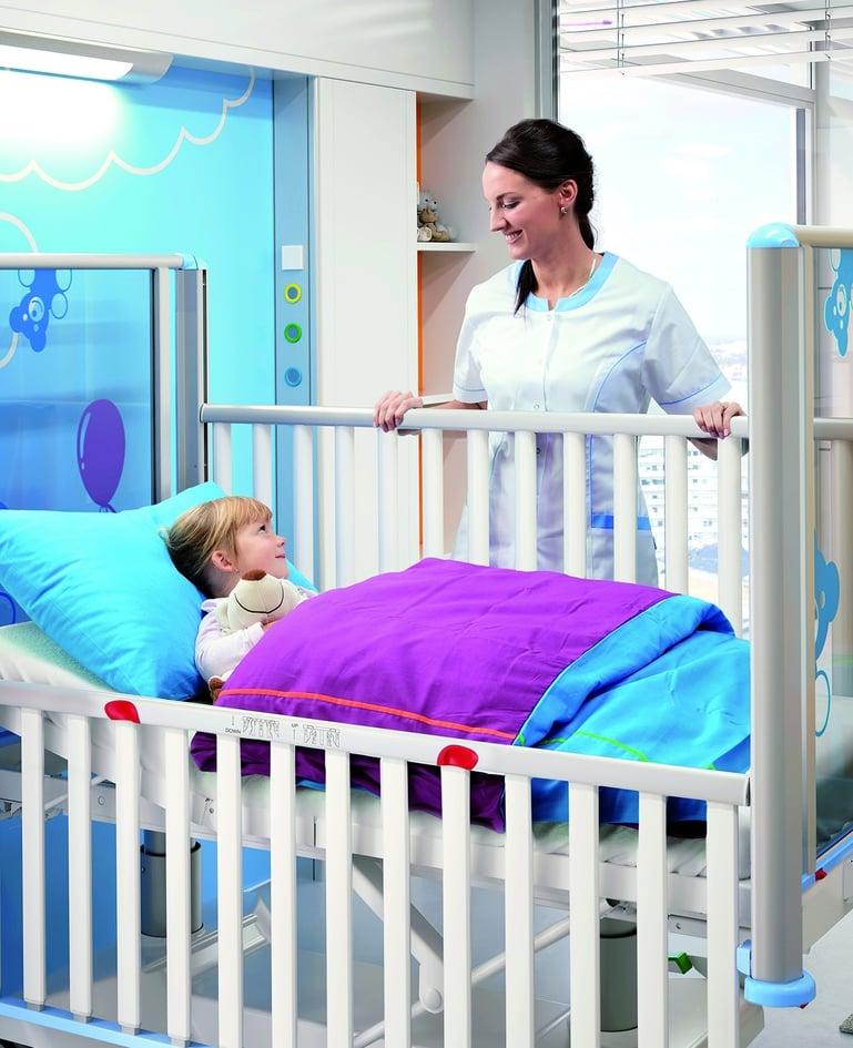 Kind in modernem Kleinkinderbett, Betreuerin steht an Seitensicherung und lächelt Kind an