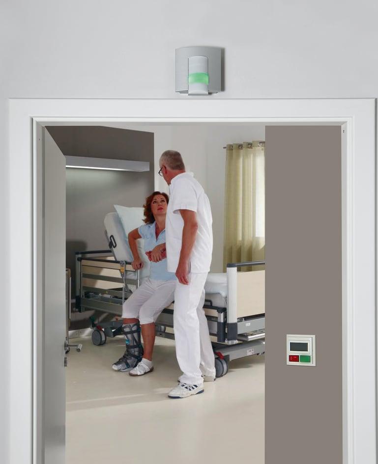 Ein Betreuer steht bei der Patientin, die durch ihr Aufstehen das Rufsystem aktiviert hat, am Bett und betreut sie