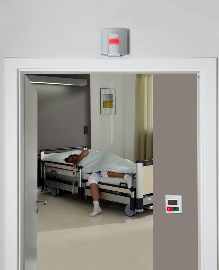 Patientin steht aus einem Spitalbett auf und an der Zimmertür leuchtet ein rotes Nachtlicht auf, das das Rufsystem aktiviert