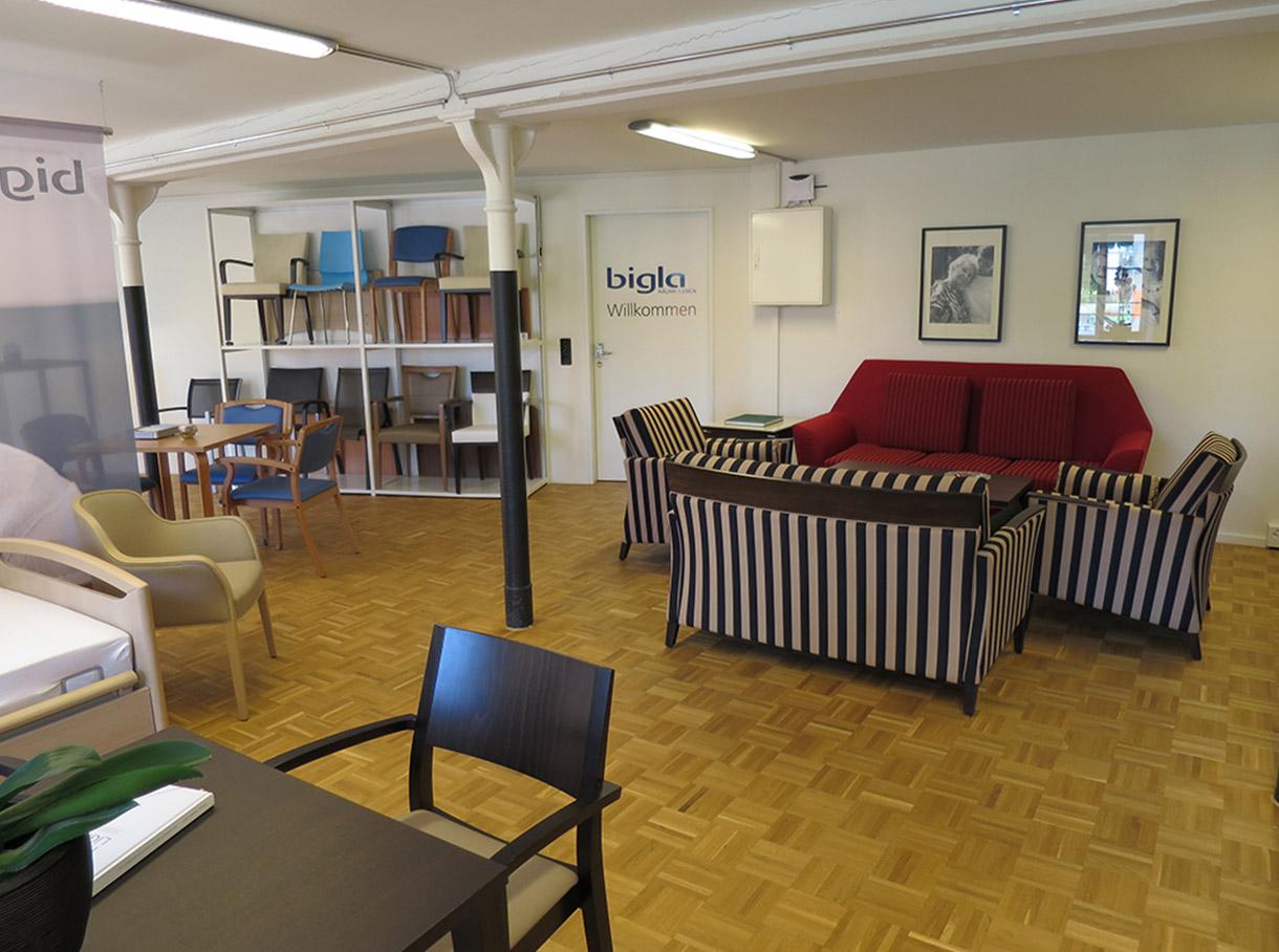 Pflegebett mit Besuchersessel und kleinem Tisch vor einem grossen Werbebanner im Showroom in Effretikon
