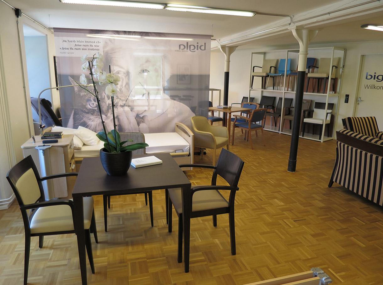 Bunt bezogenes Pflegebett mit Sofa, Sessel und Nachttisch im Showroom Effretikon