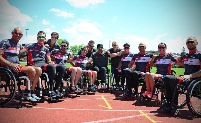 Das Para Racing Team mit 9 Athletinnen und Athleten im Rollstuhl bilden einen Halbkreis, drei Trainerpersonen stehen dahinter