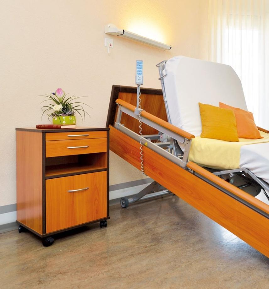 Pflegebett mit bunten Kissen und speziellem Design. Rahmen des Betts schräg aufgerichtet. Matratze formt Sitzposition. Handbedienung in Halterung am Bett. Nachttisch mit Rollen und Blumen