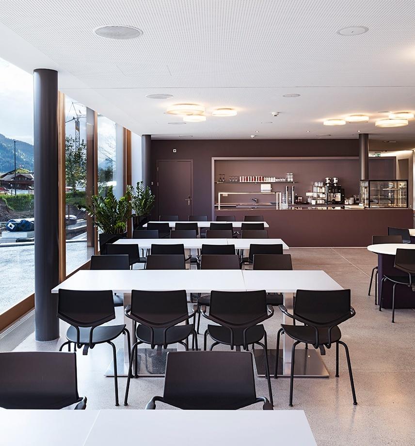 Helle Caféteria mit Panoramafenstern. Lange Tische mit Stühlen. Gepflegte Caféteria-Theke
