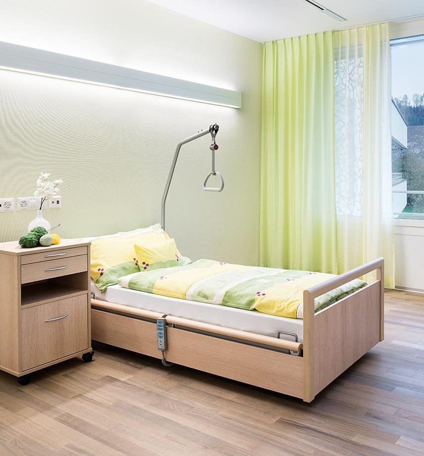 Helles Spitalzimmer mit hellgrünen Vorhängen und Niedrigpflegebett mit passender Bettwäsche. Nachttisch mit Blumenvase und Stricksachen. Handbedienung am Bettrahmen